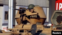 在迪亚巴克尔一条主要街道上,一名土耳其陆军士兵守卫在机关枪后面。(2014年10月9日)