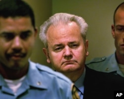 FILE - Slobodan Milosevic, center, enters the courtroom to appear before the court of the International Criminal Tribunal for the former Yugoslavia in The Hague, the Netherlands, Dec. 11, 2001.