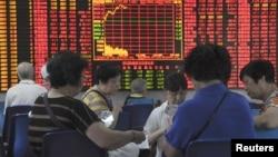 Para investor China bermain kartu di depan layar informasi bursa saham di Shanghai, China, Rabu (9/9).