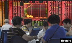 Investors play cards in front of an electronic board showing stock information at a brokerage house in Shanghai, China, Sept. 9, 2015.
