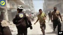 Bức ảnh này được trích ra từ video, ghi lại hình ảnh các thành viên của Lực lượng Phòng vệ Dân sự Syria bỏ chạy sau các cuộc không kích và nã pháo tại Aleppo, Syria, ngày 24 tháng 04 năm 2016.