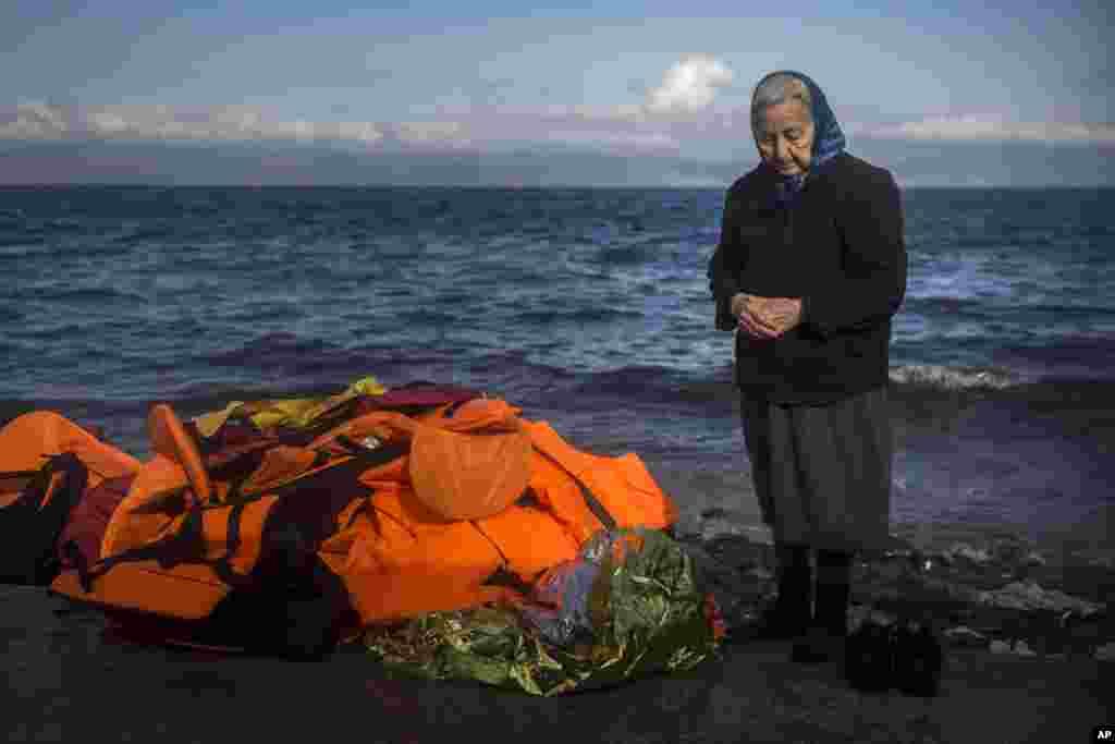 Một người phụ nữ địa phương lớn tuổi đứng trên một bãi biển trên đảo Lesbos của Hy Lạp, bên cạnh một đống áo phao, sau khi người tị nạn và di dân tới từ bờ biển Thổ Nhĩ Kỳ.