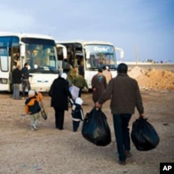Palestinian refugees head towards the buses that will take them to Syria after years in Al Tanf refugee camp between the borders of Syria and Iraqi, Feb 2010