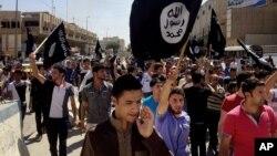 지난 6월 이라크 북부 모술에서 수니파 무장반군 ISIL의 지지자들이 깃발을 흔들며 행진하고 있다. (자료사진)