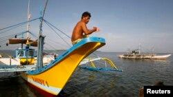 Hình tư liệu - Một ngư dân Philippines ngồi trên mũi thuyền sau khi trở về từ Bãi cạn Scarborough, ngày 10 tháng 5 năm 2012.