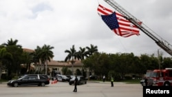A hearse carrying the casket of Aaron Feis, one of the victims of the mass shooting at Marjory Stoneman Douglas High School, drives past a U.S. flag, placed on a fire truck, during his funeral service in Coral Springs, Florida, U.S., Feb. 22, 2018.