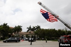 FILE - A hearse carrying the casket of Aaron Feis, one of the victims of the mass shooting at Marjory Stoneman Douglas High School, drives past a U.S. flag, placed on a firetruck, during his funeral in Coral Springs, Fla., Feb. 22, 2018.
