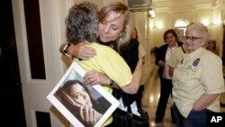 지난해 존엄사로 세상을 떠난 브리타니 메이나드 양의 어머니가 9일 캘리포니아 주가 존엄사 합법 판정을 내린 후 딸의 사진을 들고 포옹하고 있다.