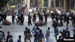 Polisi anti huru-hara dan para pengunjuk rasa saling melempar batu dalam bentrokan dekat lapangan Tahrir, Kairo, Mesir (28/11). Presiden Morsi berencana untuk menyampaikan pidato di tengah pemboikotan panel oleh kaum Kristen dan liberal yang akan melakukan pemungutan suara terkait rancangan konstitusi, hari ini (29/11).