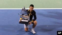 Novak Djokovic dari Serbia dengan piala Kejuaraan Dubai (2/3). (AP/Regi Varghese)