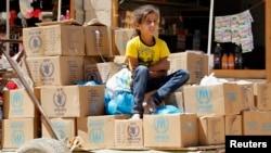 Một bé gái Syria tị nạn ngồi trên các hộp đồ viện trợ tại trại tị nạn Al Zaatri trong thành phố Mafraq Jordan, gần biên giới với Syria.