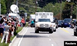 An ambulance carrying American missionary Nancy Writebol, 59, who is infected with Ebola in West Africa arrives past crowds of people taking pictures at Emory University Hospital in Atlanta, Georgia, Aug. 5, 2014.