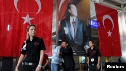 Men greet each other in front of Turkish flag and picture of modern Turkey's founder Mustafa Kemal Ataturk at Istanbul Ataturk airport, Turkey, following yesterday's blast, June 29, 2016.