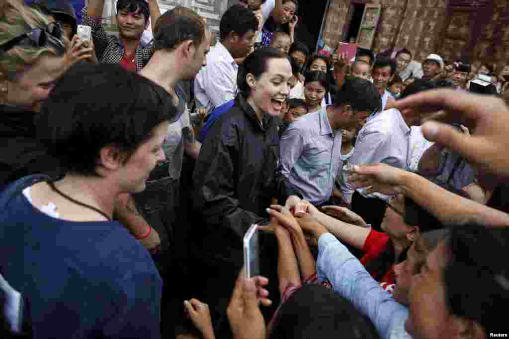 UNHCR special envoy Angelina Jolie Pitt (C) shakes hand with Kachin ethnic refugees as she visits Jam Mai Kaung IDP camp in Myitkyina capital city of Kachin state, Myanmar.