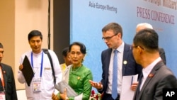 FILE - Aung San Suu Kyi talks with Estonia Foreign Minister and a representative of EU Sven Mikser, second right, as they leave a press conference after the Asia Europe Foreign Ministers (ASEM) at Myanmar International Convention Centre (MICC), Nov. 21,