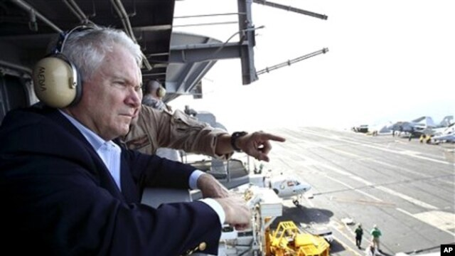 Defense Secretary Robert Gates watches flight operations aboard the USS Abraham Lincoln in the Arabian Sea', 6 Dec 2010