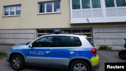 FILE - A police car standing in front of a building where a suspected Salafist Islamist extremists was believed to live, in Oberursel near Frankfurt, Germany, April 30, 2015.