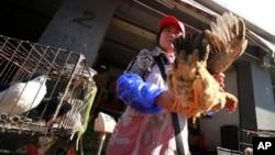 4月2 日在中國上海的一個市場一名商販用手拿著一隻雞叫買。