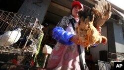 Một người bán gà tại một khu chợ ở Thượng Hải, Trung Quốc, 2/4/13. Tiếp xúc trực tiếp với gia cầm bị bệnh có nguy cơ bị nhiễm virút cúm gà