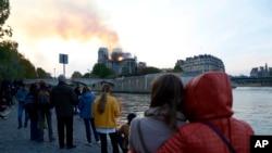 Para pengunjung menyaksikan dari kejauhan saat api dan asap membubung dari Katedral Notre Dame yang terbakar di Paris, Senin, 15 April 2019.