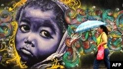 A woman passes by a graffiti in Salvador da Bahia, Brazil, June 18, 2013.
