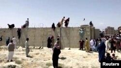 阿富汗人爬上喀布爾國際機場帶有鐵絲網的圍牆要進入機場。 (2021年8月16日)