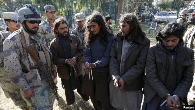 Taliban militants, right, who were arrested by Afghan border police, stand during a presentation of seized weapons and equipment, Jalalabad, Dec. 29, 2015.