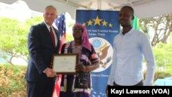Les représentants de la coopérative la Semence Divine, recevant la convention de financement de l'Ambassadeur Eric Stromayer, Lomé, le 1er octobre 2019. (VOA/Kayi Lawson)