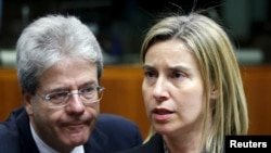 European Union foreign policy chief Federica Mogherini and Italian Foreign Minister Paolo Gentiloni (L) attend a meeting of European Union foreign and defence ministers at the EU Council in Brussels, Belgium, May 18, 2015.