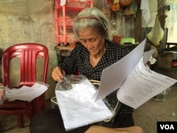"""Mommy"" is siting in front of her house looking for documents proving the house belongs to her family after she was released in April. (Phorn Bopha/VOA Khmer)"