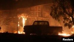 Una estructura resulta quemada mientras fuertes vientos impulsan un incendio forestal cerca de Santa Paula, California, el martes, 5 de diciembre de 2017.