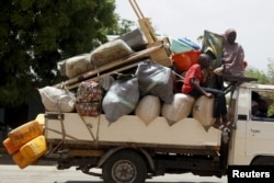 FILE - People travel in a truck with their belongings as they return after the Nigerian military recaptures the town of Michika from Boko Haram, Adamawa state, May 10, 2015.