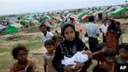 Seorang perempuan muslim Rohingya menggendong bayinya yang lahir di kamp penampungan sementara (foto: dok). Banyak anak-anak di kamp-kamp pengungsian tidak bersekolah lebih dari setahun.