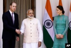 Britain's Prince William, left, and his wife Kate, the Duchess of Cambridge, right, are greeted by Indian Prime Minister Narendra Modi as they arrive for a lunch with him, in New Delhi, India, Tuesday, April 12, 2016.