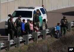 FIEL - A woman and children stand amidst U.S. Border Patrol agents after crossing illegally over the border into San Diego, California, as seen from Tijuana, Mexico, Dec. 9, 2018.