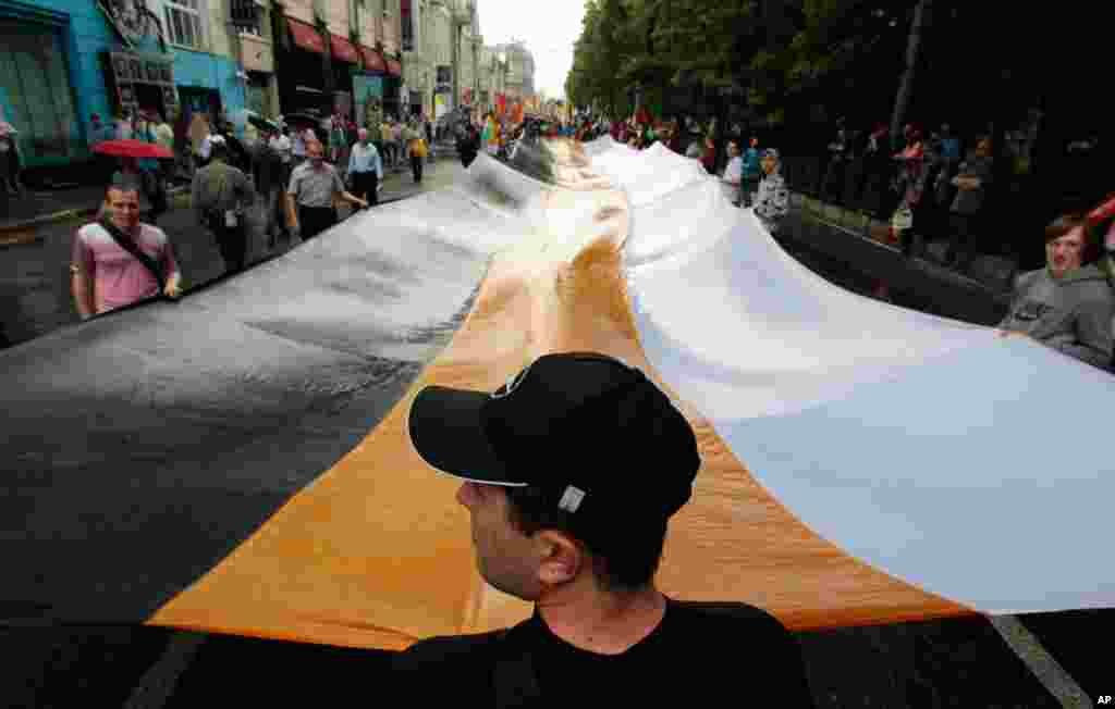 Activists hold a huge Russian Empire flag during an anti-government protest in Moscow June 12, 2012. Thousands of Russians said they would defy Kremlin pressure and attend a march in Moscow on Tuesday to protest against President Vladimir Putin, shrugging