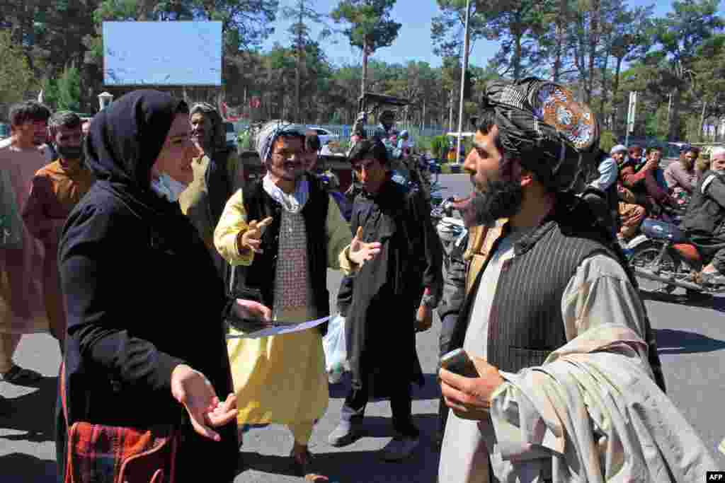 An Afghan woman protester speaks with a member of the Taliban during a protest in Herat.