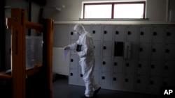 2020年4月3日,比利時身穿防護服的工人攜帶一名死於新冠病毒死者的骨灰。