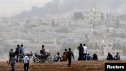 人们在山上观看科巴尼在战火中浓烟滚滚(2014年10月11日)