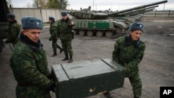 FILE - Russia-backed rebels unload 120mm mortars from trucks near Luhansk, eastern Ukraine, Oct. 15, 2015.