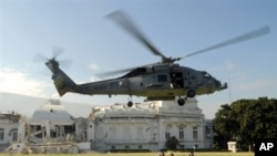 US Navy helicopter lands next to US troops in front of heavily damaged presidential palace in Port-au-Prince 19 Jan 2010