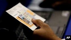 Một giới chức xem xét ảnh của cử tri tại một địa điểm bầu cử ở Austin, Texas.