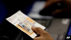 一名选民拿着身份证进行投票