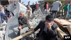 Survivors gather around a collapsed building in Ercis, near the eastern Turkish city of Van, October 24, 2011. The death toll in an earthquake which shook southeast Turkey on Sunday has risen to 239 people, with around 1,300 people injured, Deputy Prime M