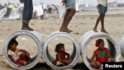 FILE - Children sitting inside cement water pipes play on the Marina beach in the southern Indian city of Chennai, Oct. 10, 2013.