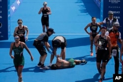 Mexico's Cecilia Perez, center, collapses after competing in a women's triathlon test event at Odaiba Marine Park, a venue for marathon swimming and triathlon at the Tokyo 2020 Olympics, Thursday, Aug. 15, 2019, in Tokyo. Olympic officials say they are concerned about high temperatures in Tokyo during the Games.