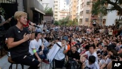FILE - Cantonese pop singer and outspoken activist Denise Ho, left, performs during a free concert at a street in Hong Kong, June 19, 2016.