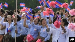 Cambodian students wave their national flags during a ceremony to celebrate the country's 59th Independence Day from France, at the Independence Monument in Phnom Penh, Cambodia, Friday, Nov. 9, 2012. (AP Photo/Heng Sinith