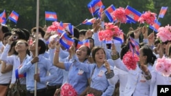 Cambodian students wave their national flags during a ceremony to celebrate the country's Independence Day from France.