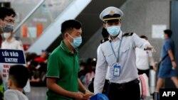Staf Pusat Pengendalian Penyakit Vietnam (kanan) membantu para penumpang saat antre pemeriksaan suhu di terminal keberangkatan bandara internasional Danang, 27 Juli 2020. (Foto oleh Hoang Khanh / AFP)